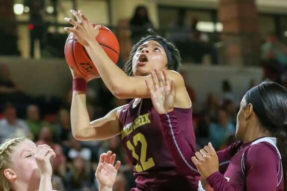 Summer Creek's Damaya Telemaque, center, finds an opening to the hoop in Tuesday night's win over Alvin.