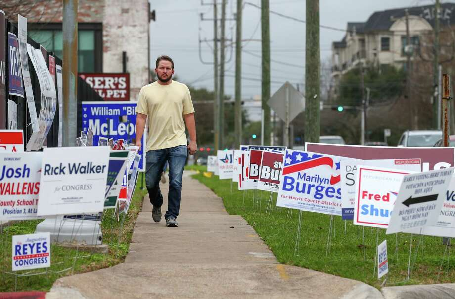 Campaign signs surround a sidewalk on West Gray Street outside the early voting station at the Metropolitan Multi-Services Center. Democrats showed a 300 percent gain and Republicans a 25 percent jump in Tuesday's totals compared to 2014. Photo: Godofredo A. Vasquez
