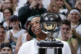 Michigan State's Miles Bridges carries the Big Ten regular-season championship trophy following the team's 81-61 win over Illinois in an NCAA college basketball game, Tuesday, Feb. 20, 2018, in East Lansing, Mich. Michigan State sealed at least a tie for the season title. (AP Photo/Al Goldis)