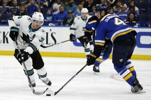 San Jose Sharks' Logan Couture (39) tries to maneuver the puck past the defense of St. Louis Blues' Carl Gunnarsson (4) during the first period of an NHL hockey game, Tuesday, Feb. 20, 2018, in St. Louis.(AP Photo/Tom Gannam)