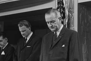 """President Lyndon Johnson prays with Dr. Billy Graham at the annual Presidential Prayer Breakfast held in Washington, D.C. The President proposed all faiths in the U.S. unite in honoring """"a fitting memorial to God who made us all."""""""