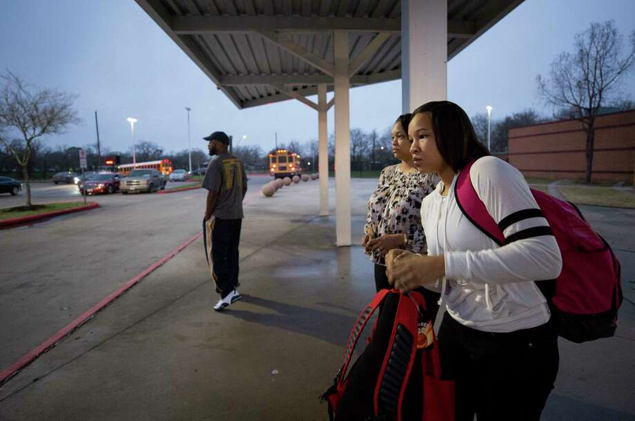 Fifteen-year-old Nia McGee, right, adjusts one of her backpacks as she gets ready to board the HISD bus that takes her to Bellaire High School Thursday, Feb. 15, 2018, in Houston. Nia, who lives in Sunnyside, takes the 10-mile bus ride to a school with more resources. Photo: Godofredo A. Vasquez, Houston Chronicle / Godofredo A. Vasquez