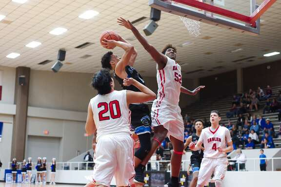 Clear Springs' Faite Williams (4) tries to put up a shot over Dawson's Lorenzo Waddy (52) Tuesday, Feb. 20 at Pasadena ISD Phillips Field House.