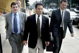 Alfred Lenoci Jr. (center) leaves the Federal Courthouse in New Haven, Conn. after being sentenced to 18 months in prison for his role in the corruption trial of Bridgeport Mayor Joe Ganim on July 21, 2003. On the left is Alfred Lenoci Sr. and on the right is his lawyer, J. Robert Gulash.
