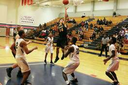 Liberty junior J. J. Slack drives the lane and challenges the Bulldog defense with a layup in the paint.