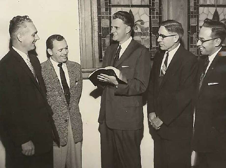 From left, Howard Hicks, general manager of the Beaumont Chamber of Commerce; the Rev. W.W. Kennedy of Cove Baptist Church of Orange; evangelist Billy Graham; the Rev. Frank L. Grayer, pastor of First Baptist Church of Groves; and Dr. H.E. Pickard, pastor of St. Andrew's Presbyterian Church of Beaumont, talk at the Roberts Avenue Methodist Church on Monday, Nov. 19, 1956. Enterprise file photo Photo: Enterprise Archives