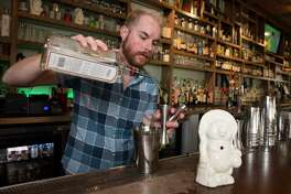 Izakaya Bar Manager Alex Coon making a Saturn cocktail to pour into a Buddha bear mug on Thursday, Feb. 8, 2018, in Houston. ( Yi-Chin Lee / Houston Chronicle )