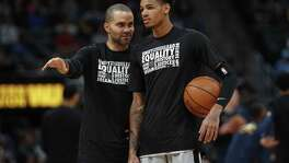 San Antonio Spurs guard Tony Parker (9) and San Antonio Spurs guard Dejounte Murray (5) in the second half of an NBA basketball game Tuesday, Feb. 13, 2018, in Denver. The Nuggets won 117-109. (AP Photo/David Zalubowski)