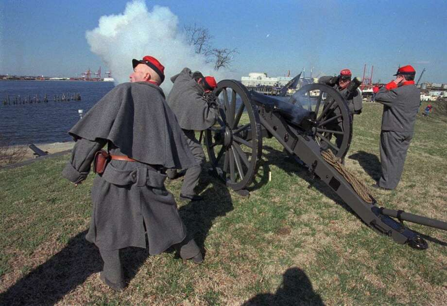 Dressed as Confederate soldiers, a cannon crew reenacts the role of land-based soldiers in the Civil War clash of the Monitor and Merrimac in March of 1862 in Hampton Roads, Virginia. Photo: File Photo / CHICAGO TRIBUNE