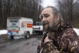 As a U-Haul truck drives away with some of his things, Robert Niewiadomski, 72, asks his friend Terry if he wants to come inside for a beer after helping Niewiadomski relocate items from his home on Willow Drive NE, which runs along the Grand River, in Grand Rapids, Mich., on Tuesday, Feb. 20, 2018. This year's flood will be the third time in 20 years that Niewiadomski has had to temporarily move out of his home. (Casey Sykes/The Grand Rapids Press via AP)