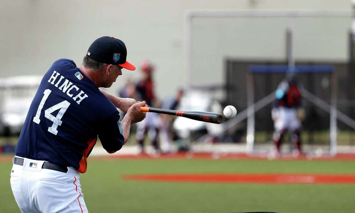 Houston Astros manager A.J. Hinch hits a ball during a drill with catchers during spring training at The Ballpark of the Palm Beaches, Wednesday, Feb. 21, 2018, in West Palm Beach.