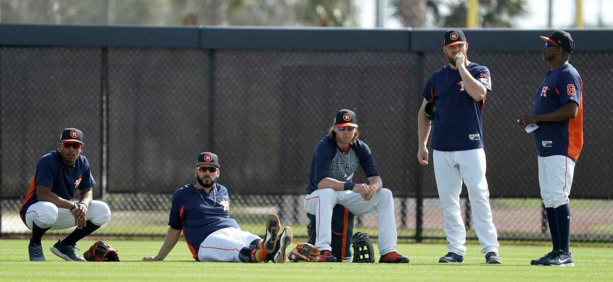 Houston Astros outfielders Tony Kemp (18), Marwin Gonzalez (9), Josh Reddick (22), Derek Fisher (21), and third base coach Gary Pettis (8) wait their turn for a drill during spring training at The Ballpark of the Palm Beaches, Wednesday, Feb. 21, 2018, in West Palm Beach.
