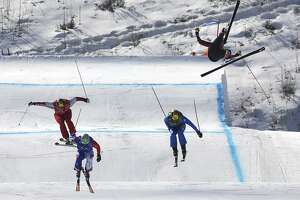 Christopher Del Bosco of Canada, right, flies through the air before crashing as Sergey Ridzik, Olympic Athletes of Russia, from left, Francois Place of France and Siegmar Klotz of Italy compete in the men's ski cross elimination round at Phoenix Snow Park at the 2018 Winter Olympics in Pyeongchang, South Korea, Wednesday, Feb. 21, 2018.