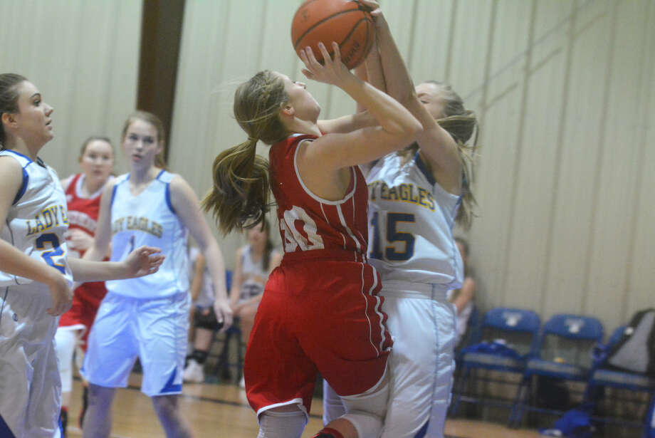 Plainview Christian Academy's Stephanie Stukey, 15, blocks a shot by Muenster Sacred Heart's Kate Speiger, 30, during the first quarter of a TAPPS Class 2A area playoff game at the Eagles' Nest Tuesday night. Sacred Heart ended PCA's season with a 53-37 victory. Photo: Skip Leon/Plainview Herald