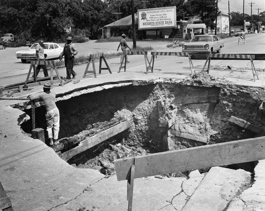 Back in October 1968 a big hole opened up in the 2800 block of White Oak in Houston when a leaking storm sewer caused a gas main to break. Initially, workmen dug a small hole to fix the gas main; but as the sewer leak continued overnight, the road collapsed in the middle of the night and the large hole was created. The collapse caused a second water main to break so White Oak was closed to traffic between Studemont and Oxford.See how sinkholes have impacted areas across the world... Photo: Roger Powers/Houston Chronicle
