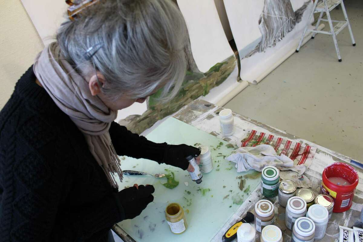 Kazaan Viveiros, Weir Farm National Site's artist-in-residence for February, touches up the paint on two of her latest pieces ?- one an image of an oak tree, the other a sycamore tree ?- on Tuesday, Feb. 20, 2018.