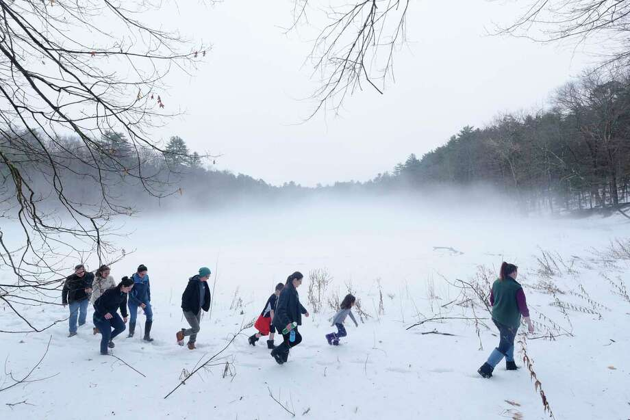 Rebecca Mullins, far right, the park educator  at Moreau Lake State Park leads a group on a family nature hike around the lake on Wednesday, Feb. 21, 2018, in Gansevoort, N.Y.  Moreau Lake State Park is open year round and on Thursday at 1:00pm, well behaved dogs on a leash and their owners can take part in the Bark Up a Tree event, a nature hike for dogs and people.  Due to warm weather the ice fishing children's clinic on Friday has been replaced with a family nature walk along the park road at 10:00am, followed by refreshments in the warming hut.  There will also be other kid activities, like a scavenger hunt, following the hike.  On the first and third Thursday of every month the park runs their Knee High Naturalist, a nature program for children ages two to five.  (Paul Buckowski/Times Union) Photo: PAUL BUCKOWSKI, Albany Times Union / (Paul Buckowski/Times Union)