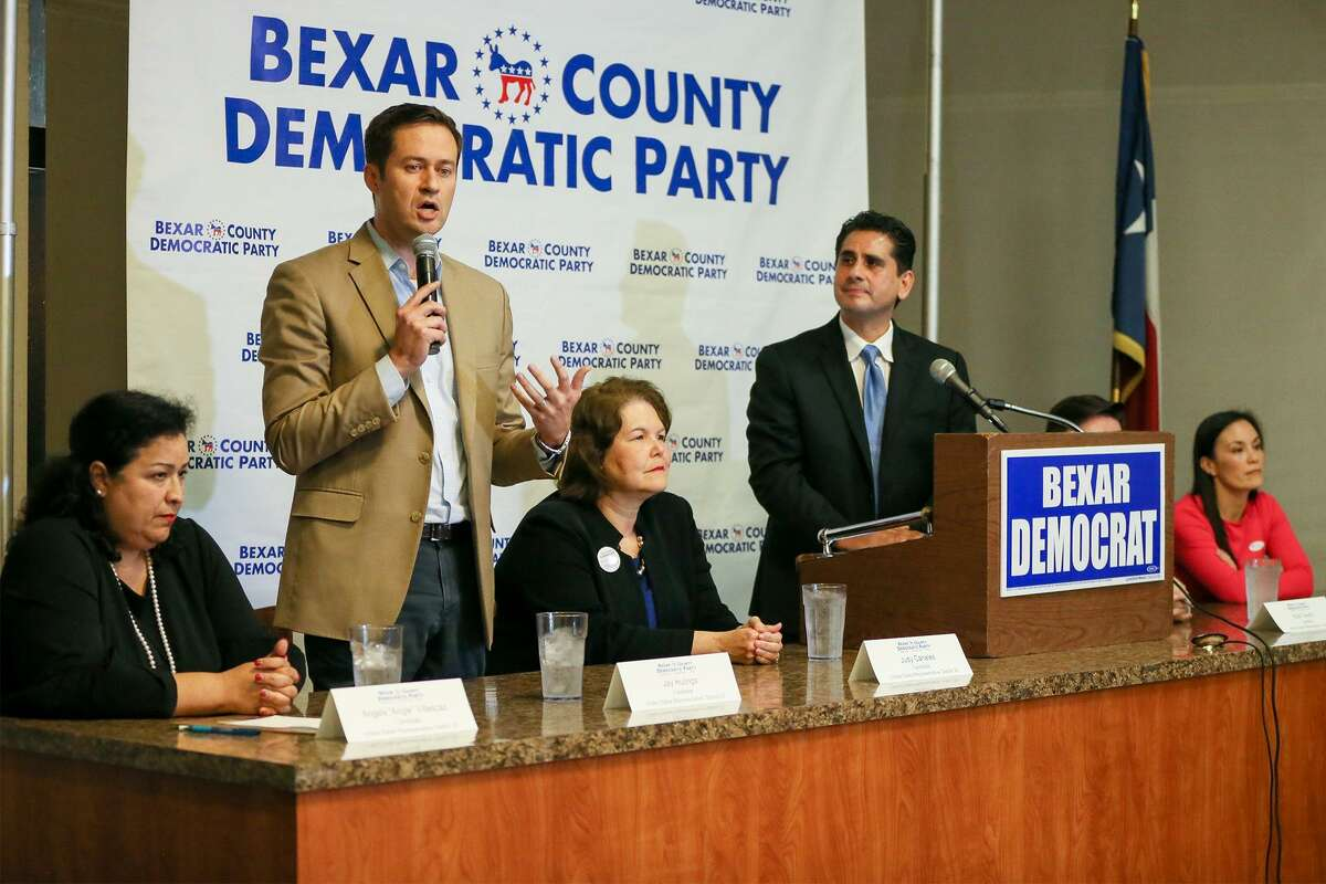 Former prosecutor Jay Hulings (second from left) speaks during a debate moderated by Bexar Democratic Party Chairman Manuel Medina (at lectern). Seated candidates for the District 23 nomination are Angela