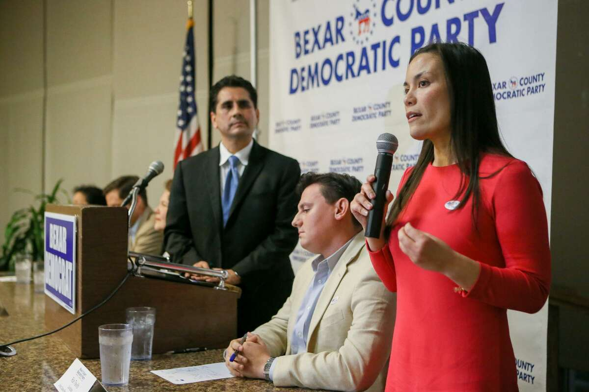 Former Air Force intelligence officer Gina Ortiz Jones (right) speaks during a debate in San Antonio in February. Standing at lectern is Manuel Medina, outgoing Bexar County Democratic Party chairman; seated is Rick Treviño, who is in the May 22 primary runoff with Jones.