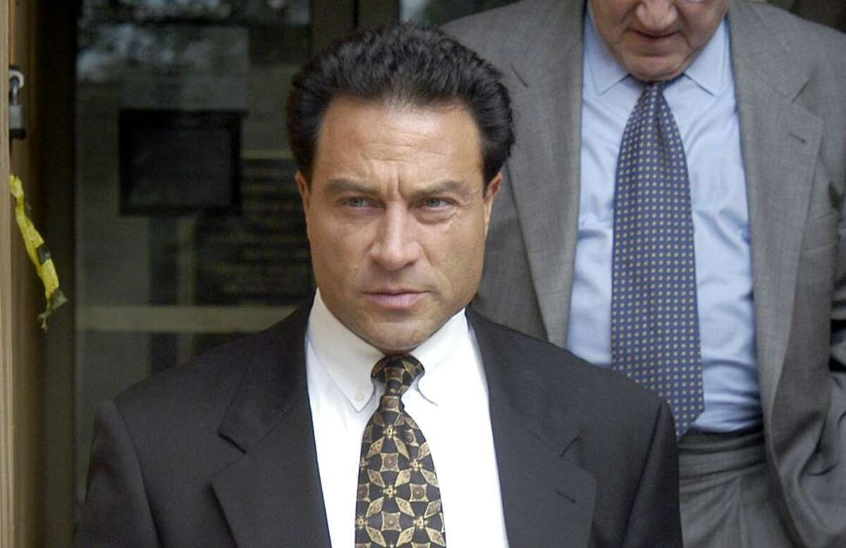 Alfred Lenoci Jr, left, leaves the Federal Courthouse in New Haven, Conn. after being sentenced to 18 months in prison for his role in the corruption trial of Bridgeport Mayor Joe Ganim on July 21, 2003. On the right is his attorney, J. Robert Gulash, and behind them is his father Alfred Lenoci Sr.