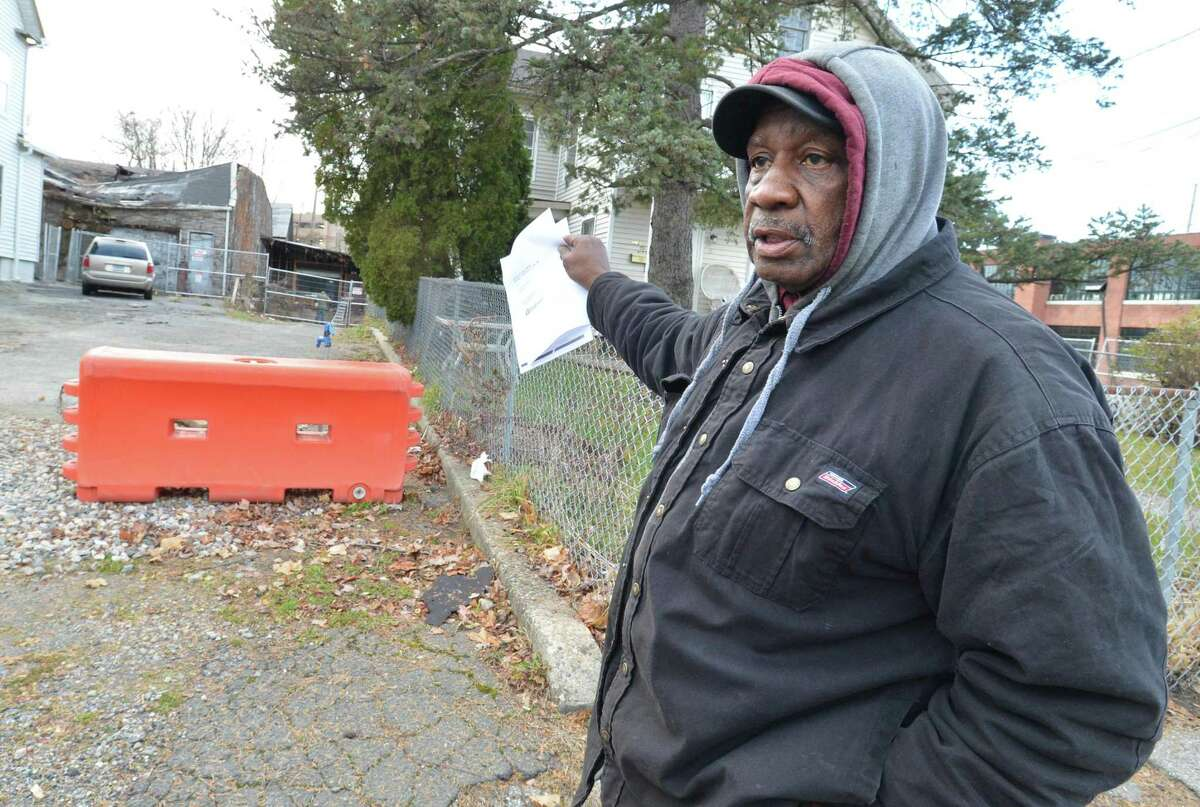 Ernie Dumas, president of the South Norwalk Citizens for Justice, points to the property at on Chestnut Street and the partially collapsed building that was a former tie factory in South Norwalk. Dumas and his group hope for city officials to enforce codes to clean up the property.