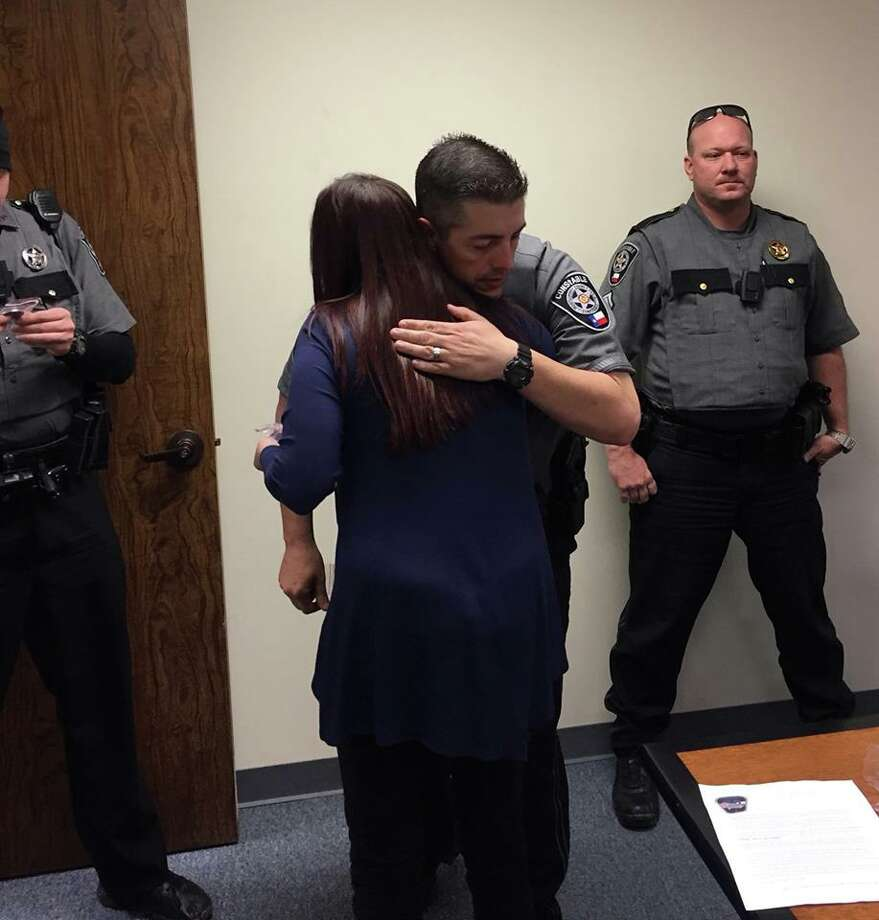 "Samantha Bachman recevives a hug from Montgomery County Precinct 4 Constable's Lieutenant Buck Clendennen after presenting the office with Challenge Coins through her project, ""One Coin at a Time."" Photo: Submitted By Samantha Bachman"