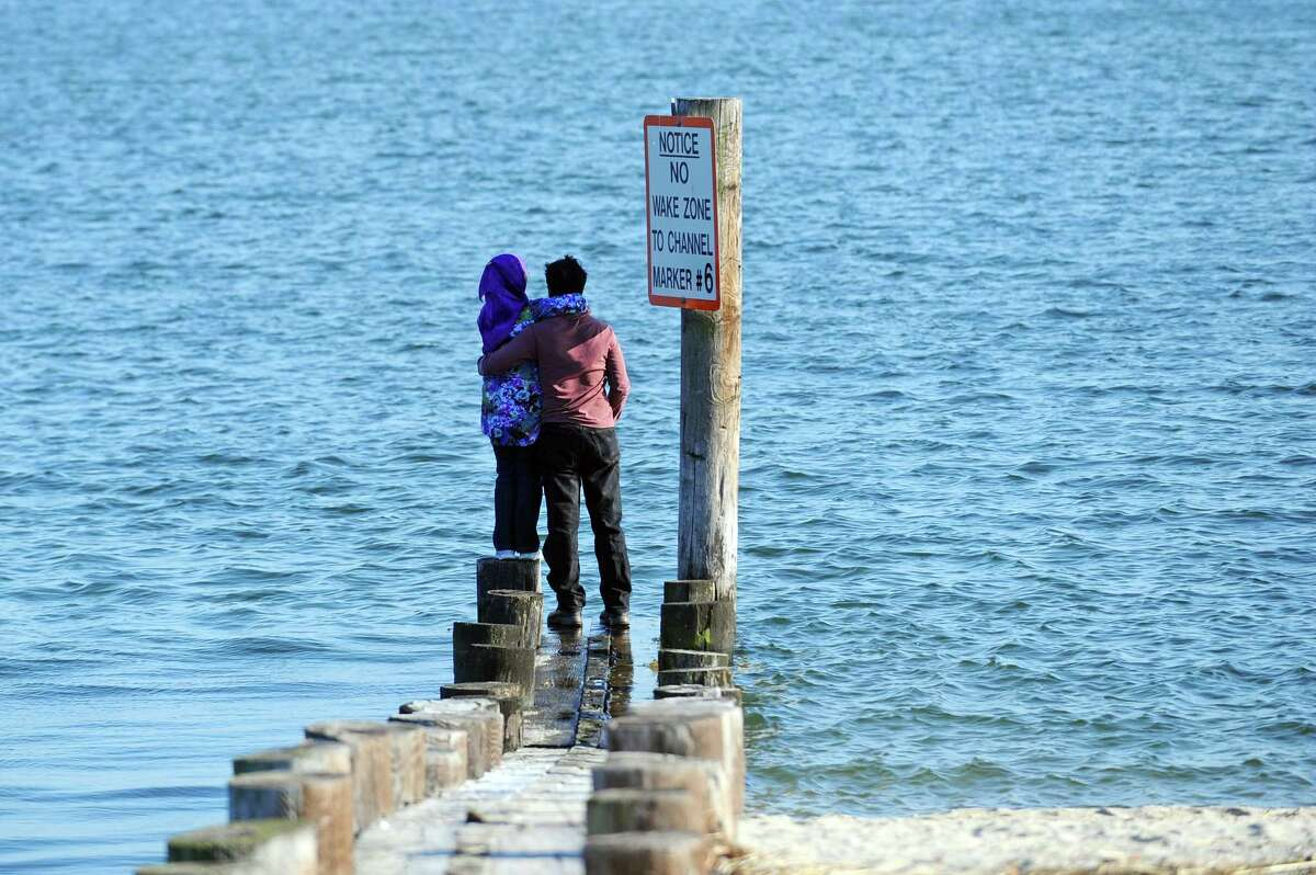 A young couple stands in embrace while looking out onto the Long Island Sound at West Beach in Stamford, Conn. on Wednesday, Feb. 21, 2018.