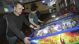 Joe Bertolini (left) and Pamela Sams play pinball during a meeting of the Stonehedge Pinball League at Stonehedge  in Akron, Ohio. The league meets twice a week.