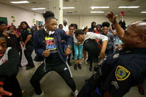 Worthing High School student Darius Scott, center, battles Houston Police officer Randall Winn, right, on the dance floor during the first Police Officer Appreciation Luncheon Wednesday, Feb. 21, 2018, in Houston. The school has partnered with the police department in an effort to increase positive interaction between students and officers.