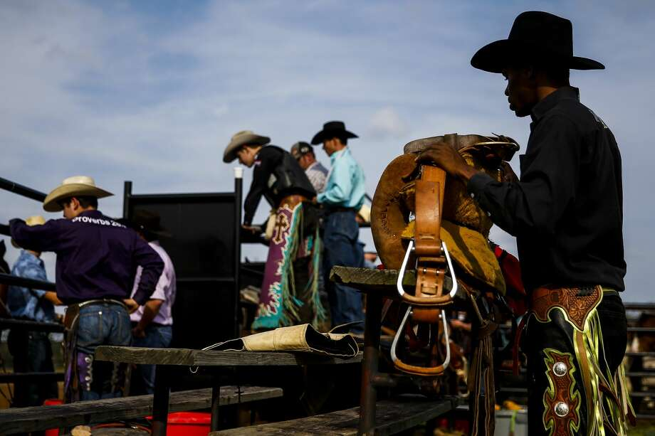 E.J. Wright prepares his saddle as he gets ready for a saddle bronc ride in the arena at the Branded for Christ Cowboy Church Sunday, Feb. 18, 2018 in Huntsville. Photo: Michael Ciaglo/Houston Chronicle