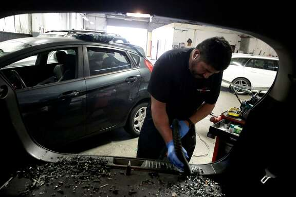 Hector Hernandez of Auto Glass Now San Francisco, vacuums up the broken glass as he prepares to replace the rear window of a vehicle that was smashed to pieces during a burglary, as seen on Thursday Jan. 25, 2018, San Francisco, Calif.