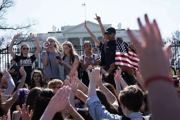 Students hold up their hands as they participate in a protest against gun violence February 21, 2018 outside the White House in Washington, DC. California legislators have introduced a package of 10 gun control bills in the wake of the Feb. 14 massacre at Marjory Stoneman Douglas High School in Parkland, Florida.