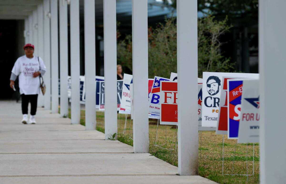 Campaign signs aligned with the walkway that leads to the front door of the early voting station at the Metropolitan Multi-Services Center Tuesday, Feb. 20, 2018.