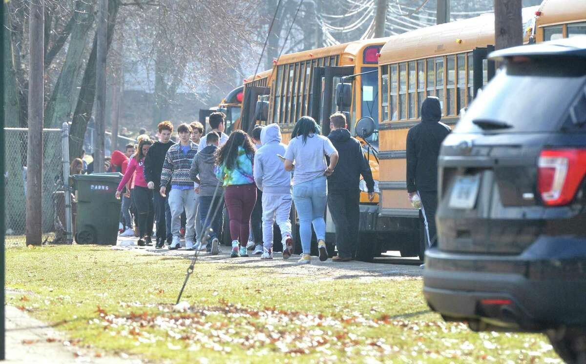 """Norwalk High School students make their way to busses for early dismissal after a """" Shelter Alert"""" was lifted due to a report of a gun at the school on Tuesday February 20, 2018 in Norwalk Conn."""