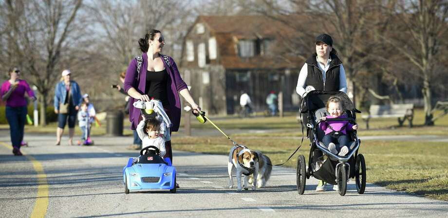 From left, Sonja Young and her daughter Adeline enjoy the warm weather as they walk with friends Christina Smith and her daughter Abigail on Wednesday at Cove Island Park in Stamford . Photo: Matthew Brown / Hearst Connecticut Media / Stamford Advocate