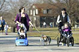 From left, Sonja Young and her daughter Adeline enjoy the warm weather as they walk with friends Christina Smith and her daughter Abigail on Wednesday at Cove Island Park in Stamford .
