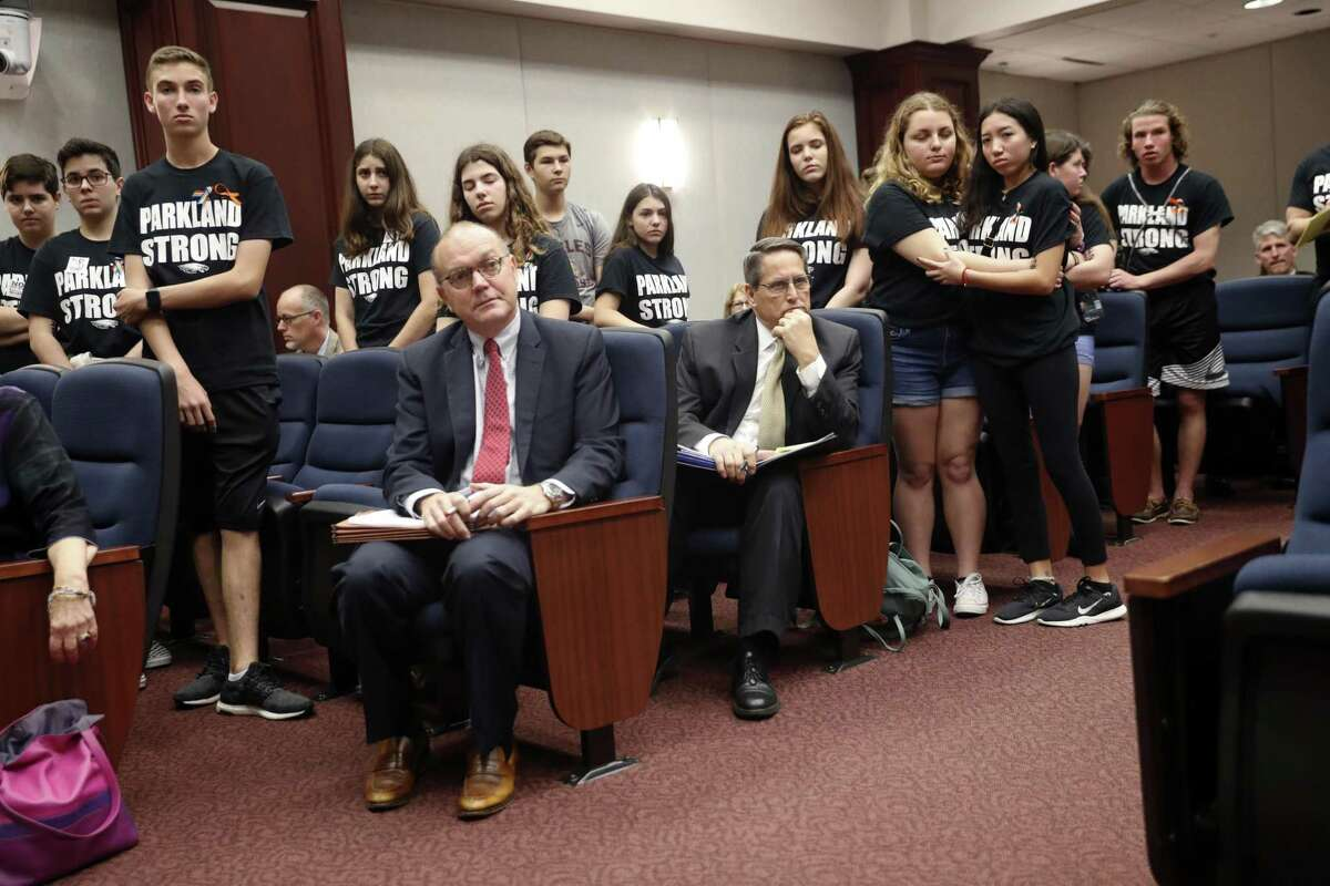 Lobbyists and attorneys listen as student survivors from Marjory Stoneman Douglas High School, where more than a dozen students and faculty were killed in a mass shooting on Wednesday, interrupt a house legislative committee hearing, to challenge lawmakers on gun control reform, in Tallahassee, Fla., Wednesday, Feb. 21, 2018.