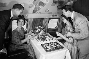 Two American women and two American men smiling in front of the buffet served on the intercontinental aeroplane 'Super G Constellation' of the airline 'TWA'. USA, 16th February 1955 (Photo by Mondadori Portfolio via Getty Images)