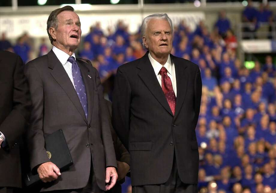 The Rev. Billy Graham, right, and former President George Bush sing during the Metroplex Mission at Texas Stadium, Thursday, Oct. 17, 2002, in Irving, Texas. (AP Photo/LM Otero) Photo: LM OTERO, STF / AP / AP