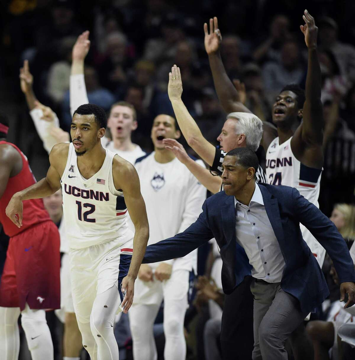 UConn head coach Kevin Ollie, right, cheers on Tyler Polley after Polley hit a three pointer during the second half against SMU on Jan. 25 in Storrs.