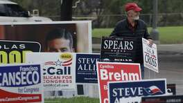 Jim Mathis looks to place a campaign sign near a San Antonio polling site on the first day of early voting. Early voting in Texas runs though March 2.