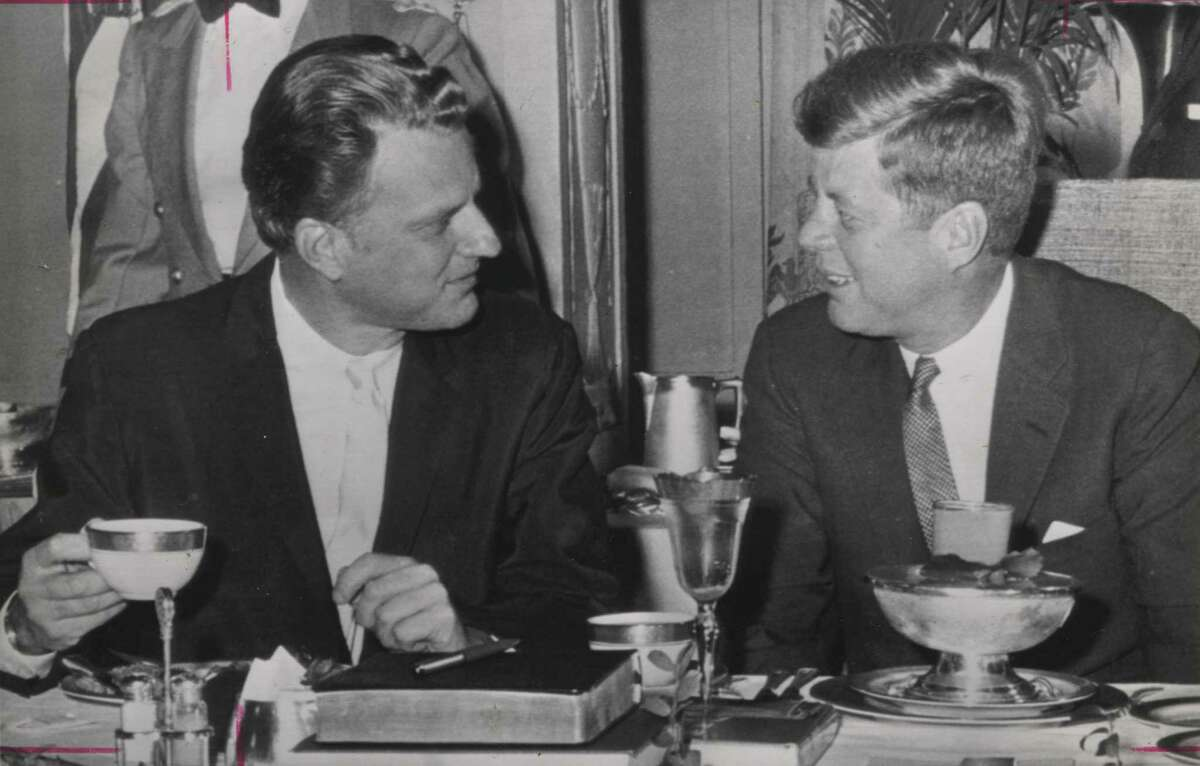 (WX3) WSHINGTON, MARCH 1, 1962 -- BREAKFAST CHAT -- President Kennedy chats with Evangelist Billy Graham at today's Tenth Annual Presidential Prayer Breakfast for Our National Leadership. Both the president and Graham spoke at the breakfast meeting, sponsored by Senate and House Prayer Breakfast Groups and the International Christian Leadership Conference of Washington. (AP WIREPHOTO) (rw51110jr) 1962