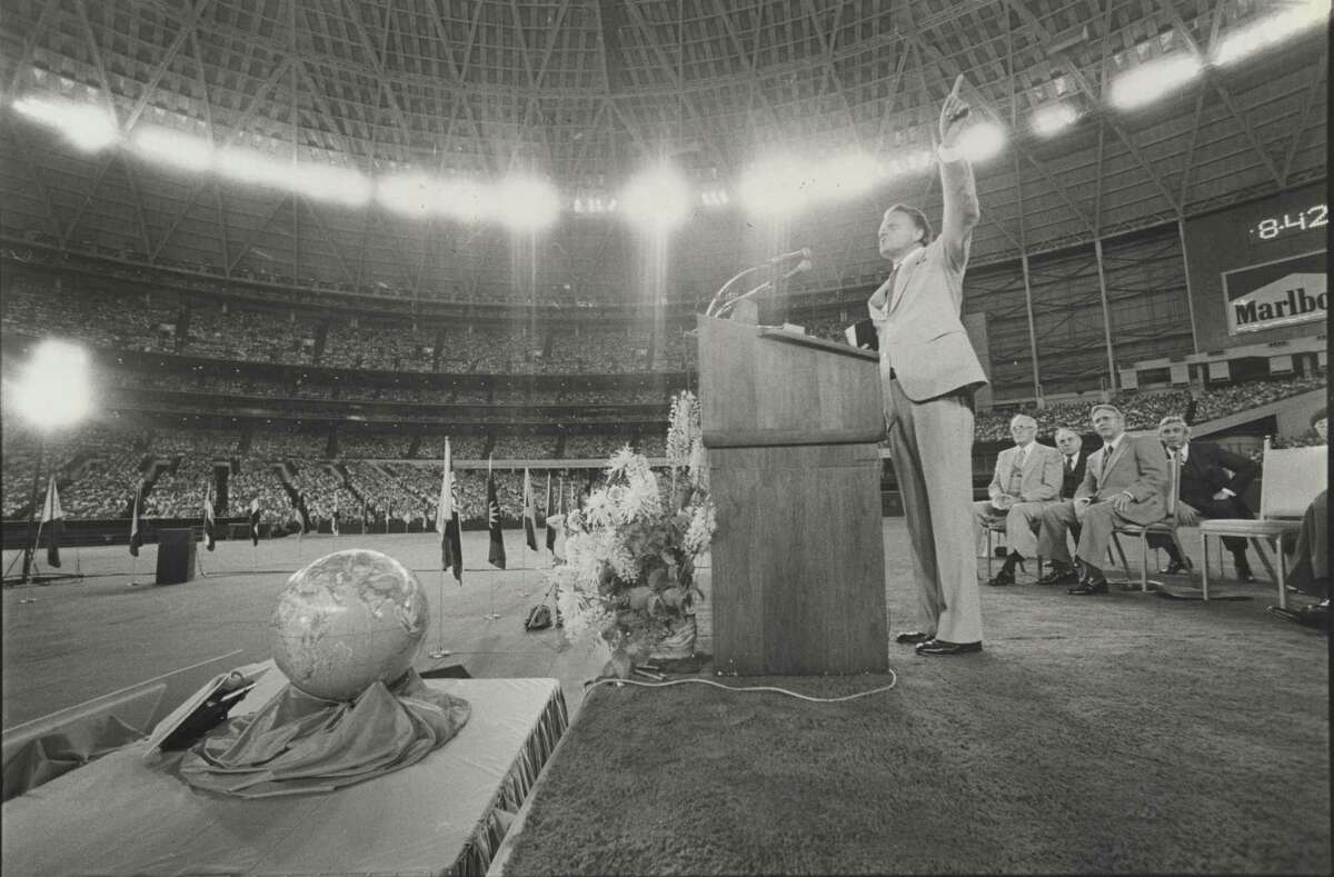 Evangelist Billy Graham, the lights of the Astrodome streaming down upon him, delivers an impassioned speech to a filled stadium.