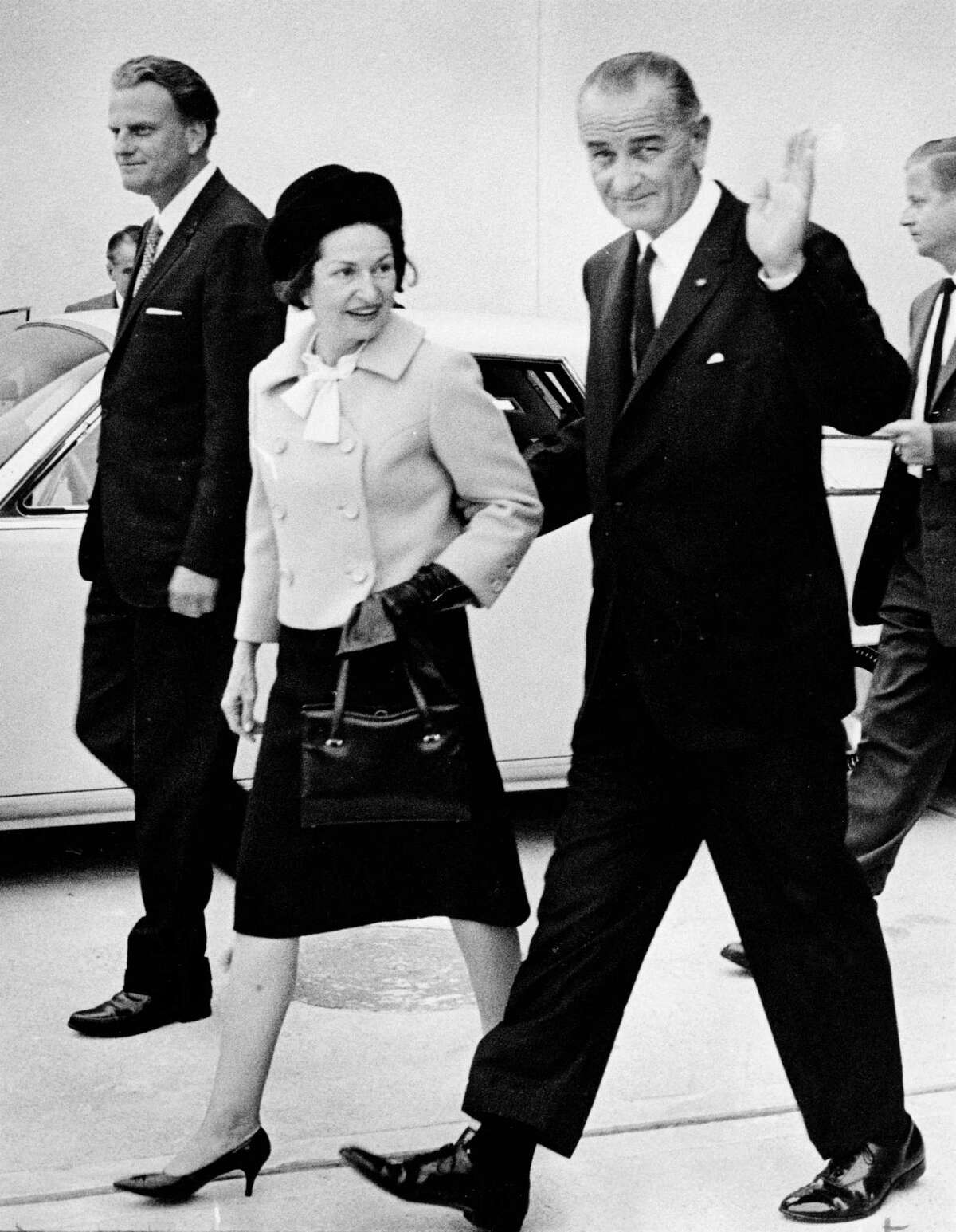 Lady Bird Johnson walks with President Lyndon Johnson and Rev. Billy Graham after an event in Houston in November 1965.