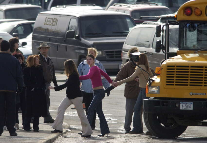 Columbia High School students hold hands as they get off a bus at Howard Goff School in East Greenbush, N.Y. on Monday, Feb. 9, 2004. Students were bused from the high school to Goff to meet their parents following a shooting at the high school earlier in the day. (Paul Buckowski/Times Union)