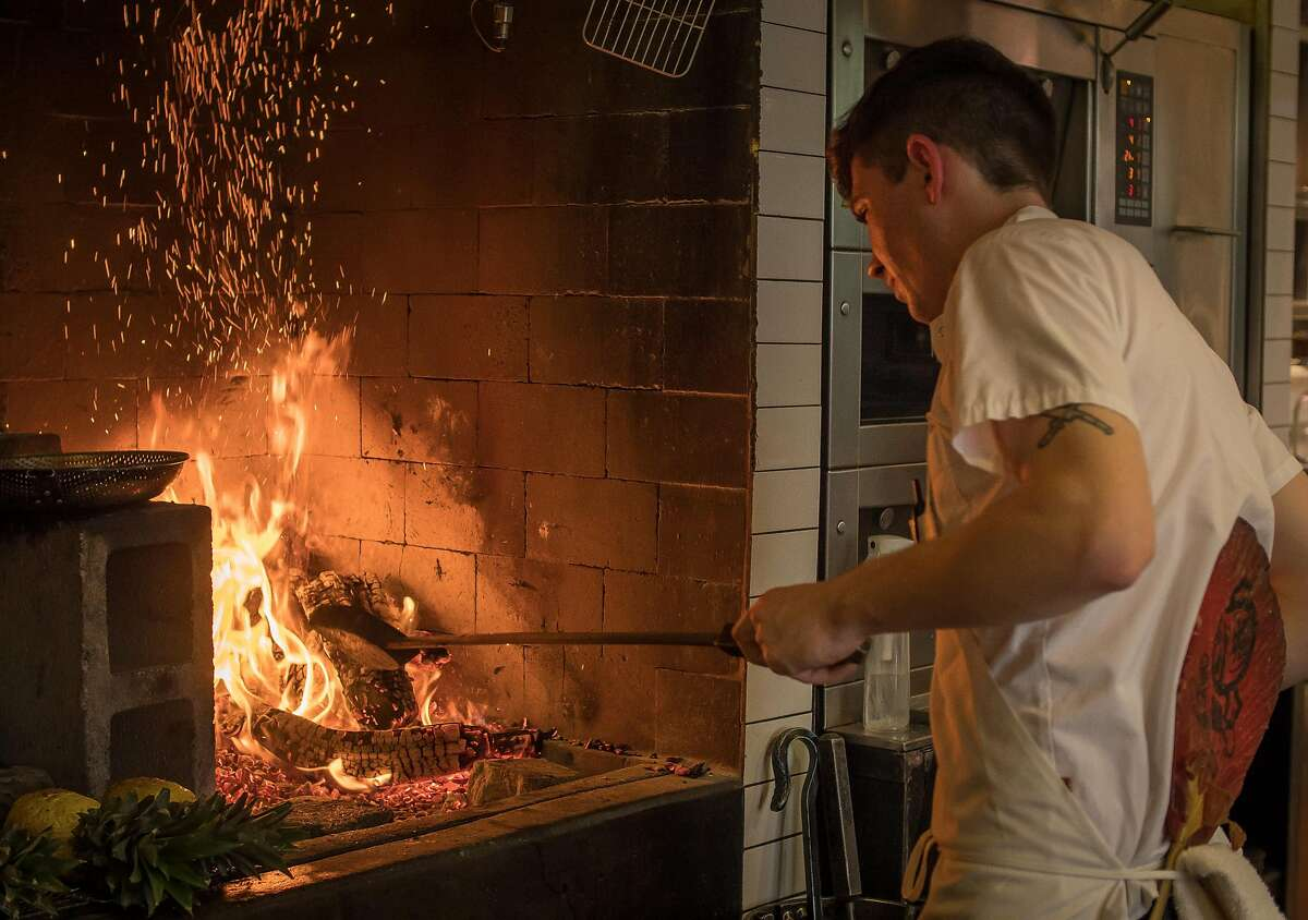 Aiden Mc Ardle tends to the fire at Saison in San Francisco, Calif., on February 16th, 2018.
