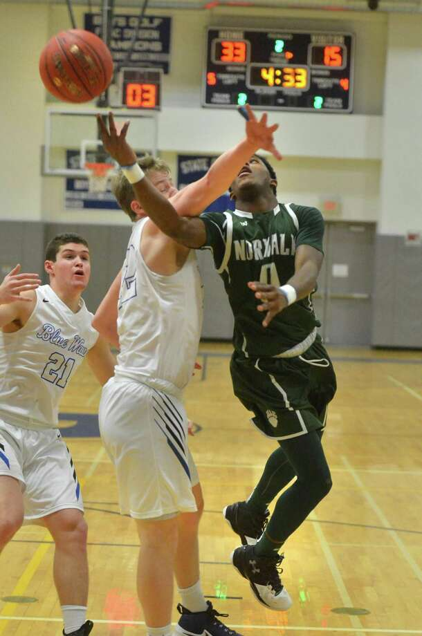Norwalk's Tyrique Langley gets a shot off around a defender during Wednesday's game against Darien in Darien. Photo: Alex Von Kleydorff / Hearst Connecticut Media / Norwalk Hour