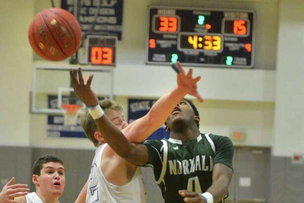 Norwalk's Tyrique Langley gets a shot off around a defender during Wednesday's game against Darien in Darien.