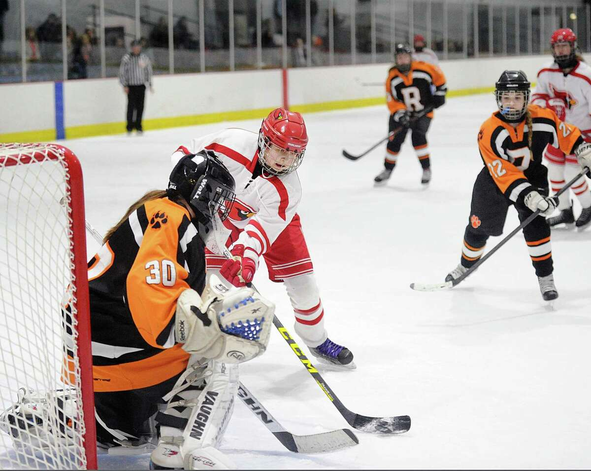 Greenwich's Emma Wingrove shoots the puck past Ridgefield goalie Kendal Mountain for the second Cardinal goal of the game during the FCIAC semifinal game on Wednesday at the Darien Ice Rink.