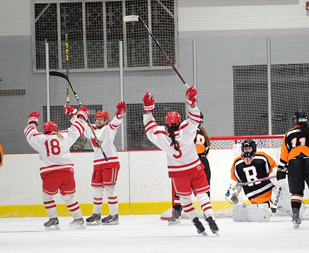 Emma Wingrove of Greenwich, second from left, and teammates Jennifer Kelly (#18), left, and Grace Fahey (#3), right, celebreate Wingrove's first period goal as Ridgefield goalie Kendal Mountain, right, looks on during the FCIAC girls semi-final ice hockey game between Greenwich High School and Ridgefield High School at Darien Ice Rink, Darien, Conn., Wednesday, Feb. 21, 2018.